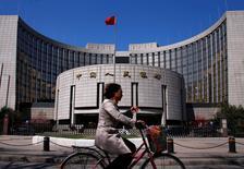Una mujer en bicicleta pasa junto a la sede del Banco Central de China, en Pekín, 3 de abril de 2014. China reducirá las tasas de interés para los préstamos concedidos a través de las líneas permanentes de crédito, una herramienta de política para inyectar liquidez en el sistema bancario, dijo el jueves el banco central. REUTERS/Petar Kujundzic