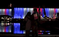 A couple looks at the grain silos in the Port of Quebec lit up in blue, white and red, the colours of the French flag, following a vigil in memory of the victims of the Paris attacks, in Quebec City, November 17, 2015.  REUTERS/Christinne Muschi