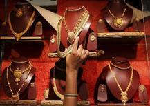 Золотые ожерелья в ювелирно магазине в Мумбаи. 13 августа 2015 года. Цены на золото растут, но рынок завершит неделю вблизи пятилетнего минимума на фоне укрепления доллара. REUTERS/Shailesh Andrade
