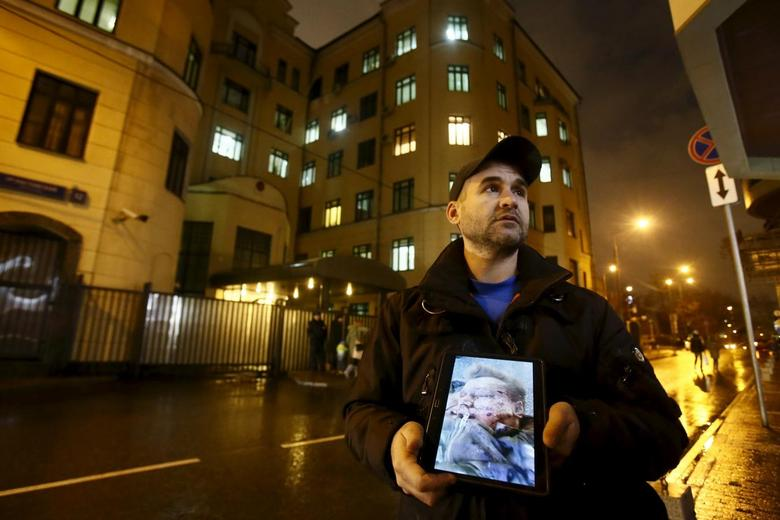 An activist holds a tablet with a picture of the lifeless body of a Russian pilot of a war plane shot down by Turkey, in front of the Turkish embassy in Moscow, Russia, November 24, 2015.  REUTERS/Maxim Shemetov