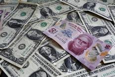 Un billete de 50 pesos mexicanos sobre un montón de billetes de un dólar en una ilustración fotográfica realizada en Ciudad de México, jul 6, 2015. México dijo el martes que el Fondo Monetario Internacional ratificó que el país continúa cumpliendo con los criterios de calificación necesarios para acceder, en caso de requerirlo, a una línea de crédito por unos 65,000 millones de dólares aprobada el año pasado. REUTERS/Edgard Garrido