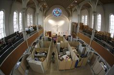 Beds for migrants, separated by impromptu partition screens, are set up inside a Protestant church in Oberhausen, Germany, October 30, 2015.   REUTERS/Ina Fassbender