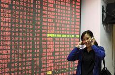 Una inversora conversa por teléfono móvil en una correduría en Hangzhou, China, oct 8, 2015. China Mobile, el mayor operador de telefonía inalámbrica de China, dijo el viernes que planea comprar el negocio de telecomunicaciones de línea fija de una empresa relacionada por 31.880 millones de yuanes (4.990 millones de dólares), para  ampliar su presencia en ese negocio en el país.  REUTERS/Stringer IMAGEN CON RESTRICCIÓN DE USO EN CHINA