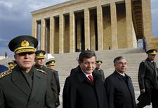 Премьер-министр Турции Ахмет Давутоглу (второй слева). начальник турецкого Генштаба генерал Хулуси Акар (слева), министр обороны Исмет Йилмаз (второй справа) после возложения венков в мавзолее Мустафы Кемаля Ататюрка в Анкаре 26 ноября 2015 года. Тело пилота сбитого российского военного самолета, погибшего в результате ракетной атаки турецких истребителей на границе с Сирией, было доставлено в Турцию вечером в субботу и будет передано России по запросу Москвы, сообщил премьер-министр Турции Ахмет Давутоглу в воскресенье. REUTERS/Umit Bektas