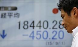 Un hombre camina delante de un tablero electrónico que muestra el índice Nikkei de Japón, afuera de una correduría en Tokio, 1 de septiembre de 2015. Las acciones japonesas bajaron el lunes, lastradas por un declive de los mercados bursátiles chinos y por datos que mostraron que la producción industrial de Japón cayó debajo de las expectativas en octubre. REUTERS/Toru Hanai