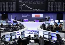 Traders work at their screens in front of the German share price index, DAX board, at the stock exchange in Frankfurt, Germany, October 1, 2015. REUTERS/Staff/remote