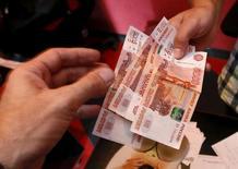 Сотрудник автосервиса принимает деньги у клиента в Красноярске 6 августа 2015 года. Рубль в плюсе утром вторника на фоне роста цен на нефть, сырьевых и ЕМ-валют, при этом динамика нефтяных котировок до заседания ОПЕК 4 декабря может выступать основным драйвером для российской валюты по завершении ноябрьского налогового периода. REUTERS/Ilya Naymushin