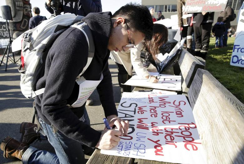 University of Washington student William Tsang, 22, of Vancouver, Canada makes a sign at a pro-refugee protest organized by Americans for Refugees and Immigrants in Seattle, Washington November 28, 2015.  REUTERS/Jason Redmond