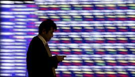 Мужчина у брокерской конторы в Токио. 1 декабря 2015 года. Китайские фондовые индексы продемонстрировали рост четвертый день подряд в четверг, практически отыграв пятничные 5-процентные потери, так как акции банков и девелоперов подтолкнули основные индексы вверх, а волнения рынка из-за мер регулятора в отношении брокерских компаний утихли.  REUTERS/Toru Hanai