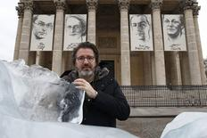 Olafur Eliasson, a Danish-Icelandic artist, poses behind a block of ice that was havested in Greenland and transported in a refrigerated container for a project called Ice Watch Paris, in Paris, France, December 3, 2015. REUTERS/Benoit Tessier