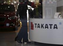 A woman stands next to a logo of Takata Corp at a showroom for vehicles in Tokyo, Japan,  November 6, 2015.  REUTERS/Toru Hanai