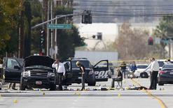 Police and Sheriff's Office Crime Scene investigators examine evidence at the scene of the investigation around an SUV where two suspects were shot by police following a mass shooting in San Bernardino, California December 3, 2015.  Authorities on Thursday were working to determine why Syed Rizwan Farook 28, and Tashfeen Malik, 27, opened fire at a holiday party of his co-workers in Southern California, killing 14 people and wounding 17 in an attack that appeared to have been planned. REUTERS/Mike Blake
