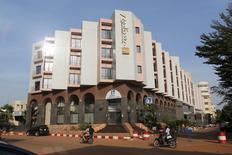 People drive motorcycles past the Radisson Blu hotel in Bamako, Mali, November 22, 2015. REUTERS/Joe Penney