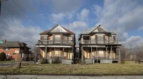 Two boarded-up, vacant houses are seen in a once vibrant neighborhood in Detroit, Michigan December 3, 2015.  REUTERS/Rebecca Cook
