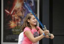"""Una niña juega con un sable laser afuera de los estudios de Disney en Hollywood, Orlando, Florida 4 de diciembre de 2015. La actriz Daisy Ridley de """"La Guerra de las Galaxias"""" sonríe en la portada de la revista Glamour, la joyería Kay Jewelers vende collares con dijes de soldados imperiales y se emiten anuncios de la nueva película """"El despertar de la Fuerza"""" durante el 'reality show' de Kim Kardashian. REUTERS/Scott Audette"""
