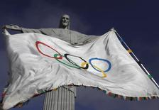 """The Olympic Flag flies in front of """"Christ the Redeemer"""" statue during a blessing ceremony in Rio de Janeiro August 19, 2012. REUTERS/Ricardo Moraes/Files"""