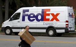 Un camión de reparto de la firma de mensajería FedEx en Wilmette, EEUU, oct 27, 2015. La empresa de envíos FedEx Corp reportó el miércoles ganancias netas trimestrales superiores a las esperadas, y dijo que mayores márgenes, recortes de costos y menores tasas impositivas efectivas contrarrestaron la debilidad de la producción industrial y el comercio a nivel global.  REUTERS/Jim Young