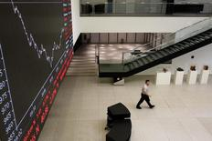 Las acciones europeas subían en las primeras operaciones del jueves después de que los inversores vieran la subida de tipos de interés por parte de la Reserva Federal de Estados Unidos por primera vez en casi una década como un signo de confianza en la mayor economía del mundo. En la imagen de archivo, un hombre pasa por el panel de información que muestra la evolución de FTSE 100 en la bolsa de Zúrich, el 9 de agosto de 2011. REUTERS/Christian Hartmann
