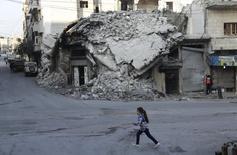 Девочка проходит мимо разрушенного дома в городе Мааррет-эн-Нууман в проивнции Идлиб, Сирия 21 декабря 2015 года. Организация объединённых наций рассматривает варианты упрощённого мониторинга соблюдения возможного режима прекращения огня в Сирии, который сведёт риски к минимуму и будет зависеть, главным образом, от сирийских представителей, сообщили дипломатические источники. REUTERS/Khalil Ashawi
