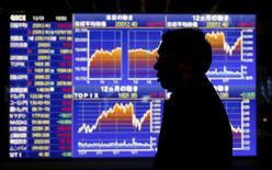 Un hombre camina delante de un tablero electrónico que muestra el movimiento reciente del índice Nikkei de Japón, afuera de una correduría en Tokio, Japón, 1 de diciembre de 2015. Las bolsas de Asia subían el martes impulsadas por las ganancias en Wall Street y ante cierta estabilidad en los precios del crudo, aunque las ganancias eran limitadas por la cautela antes de los feriados de esta semana. REUTERS/Toru Hanai