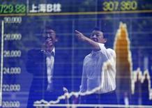 Personas se reflejan en una gráfica que muestra el índice Nikkei, afuera de una correduría en Tokio, Japón, 29 de septiembre de 2015. Las acciones japonesas bajaron levemente el martes en una sesión con un débil volumen de negocios y sin una dirección clara, debido a que muchos inversores se abstuvieron de participar antes del cierre del mercado por un feriado nacional el miércoles. REUTERS/Issei Kato