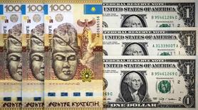На иллюстрации - тенге и американские доллары. Снимок сделан в Алма-Ате 21 августа 2015 года. Казахстан надеется занять у международных институтов развития $2 миллиарда на финансирование дефицита бюджета-2016, по доходам которого бьет падение цен на нефть. REUTERS/Shamil Zhumatov