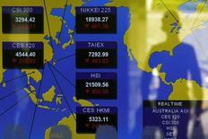 Un peatón se refleja en un panel que muestra los índices de los mercados asiáticos, en una correduría en Hong Kong, China, 24 de agosto de 2015. Las bolsas de Asia avanzaban el miércoles siguiendo la dirección de un repunte en Wall Street, mientras las principales divisas entraban en un período de calma antes de los feriados de Fin de Año y el petróleo se esforzaba por mantener un rebote modesto desde mínimos en varios años. REUTERS/Bobby Yip