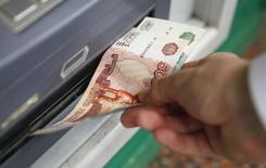 Мужчина забирает купюру из банкомата в Москве 2 сентября 2014 года. Рубль начал торги четверга ростом на фоне дорожающей нефти, на стороне российской валюты также экспортные продажи под уплату налогов, при этом рыночная ликвидность пониженная перед западным Рождеством. REUTERS/Maxim Zmeyev