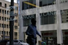 A man is reflected in a window while walking past the Bank of Canada office in Ottawa, Canada July 16, 2015. REUTERS/Chris Wattie
