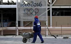 A worker walks in front of the Olympic aquatic venue for the Rio 2016 Olympic Games during the third media briefing for the Games in Rio de Janeiro, Brazil, October 6, 2015. REUTERS/Sergio Moraes