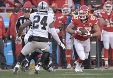 Jan 3, 2016; Kansas City, MO, USA; Kansas City Chiefs tight end Travis Kelce (87) catches a pass as Oakland Raiders free safety Charles Woodson (24) defends during the first half at Arrowhead Stadium. Mandatory Credit: Denny Medley