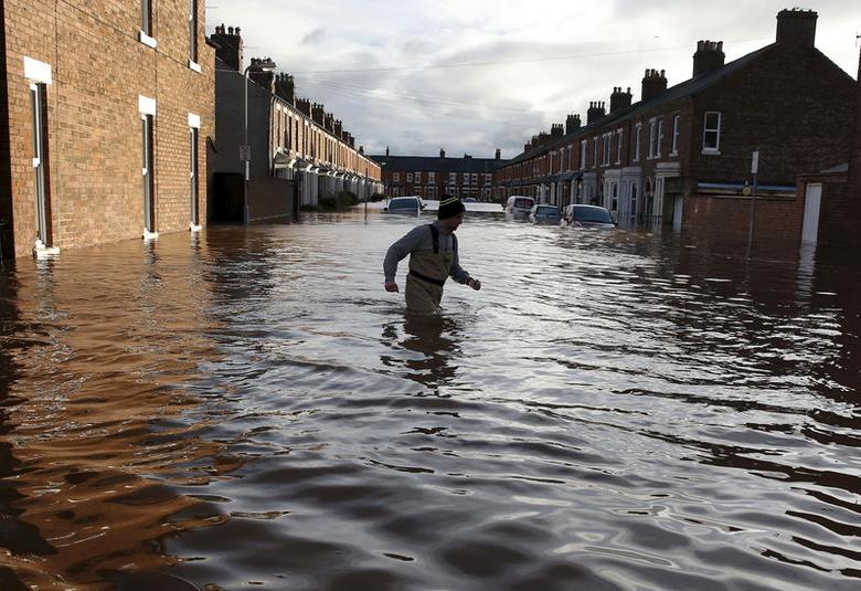 A local man wades through flood water on a residential street in Carlisle, Britain December 6, 2015. REUTERS/Phil Noble