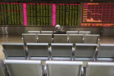 An investor sits in front of an electronic board showing stock information at a brokerage house in Beijing, China, January 4, 2016.  REUTERS/Li Sanxian