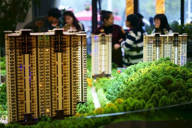 1月4日、数百万戸に及ぶ売れ残り住宅が経済に及ぼす潜在的な影響に頭を抱える中国は、農村部からきた出稼ぎ労働者(農民工)による中小都市の不動産購入を促すことで、不動産部門の負担を緩和したいと考えている。写真は昨年11月、湖北省西部の宜昌市で、不動産販売センターに置かれた新築アパートのミニチュアモデル(2016年 ロイター)