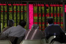 China cancelará desde el viernes su nuevo mecanismo para suspender automáticamente los mercados de renta variable, dijeron el jueves las bolsas de Shanghái y Shenzhen en sus sitios web. En la imagen, hombres mirando una pantalla electrónica que muestra información de una casa de valores de Pekín, el 5 de enero de 2016. REUTERS/Kim Kyung-Hoon