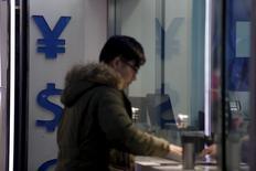 Un hombre junto a los signos del yuan chino y el dólar estadounidense, en una correduría en Shanghái, 8 de enero de 2016. El regulador cambiario de China ordenó a los bancos de algunos principales centros exportadores e importadores del país limitar las compras de dólares estadounidenses este mes, dijeron el viernes tres personas cercanas al tema, en el último intento de las autoridades por contener las salidas de capitales. REUTERS/Aly Song