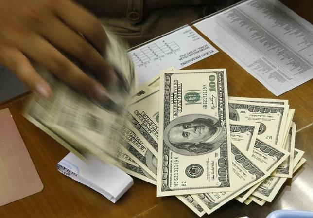 1月8日、終盤のニューヨーク外為市場はドルが上昇した。写真はドル紙幣を扱うジャカルタの両替商。2013年8月撮影(2016年 ロイター/Beawiharta)