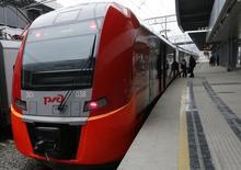 Пассажиры садятся в поезд на вокзале в Адлере, Сочи 17 января 2014 года. Российская железнодорожная монополия РЖД снизила количество перевезенных пассажиров в 2015 году на 4,3 процента до 1,024 миллиарда человек, сообщила компания в понедельник. REUTERS/Alexander Demianchuk