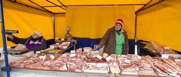 Жунщины торгуют на рынке в Минске 6 декабря 2014 года. Инфляция в Белоруссии в 2015 году замедлилась до 12 процентов с 16,2 процента годом ранее, сообщил Белстат предварительные данные. REUTERS/Vasily Fedosenko