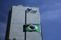 Una bandera de Brasil junto a la sede de Vale en el centro de Río de Janeiro, 15 de diciembre de 2014. El gigante minero brasileño Vale SA dijo el martes que está retirando 3.000 millones de dólares de su línea de crédito rotativa de 5.000 millones de dólares para mejorar la liquidez y cubrir posibles costos hasta que logre concretar ventas de activos. REUTERS/Pilar Olivares