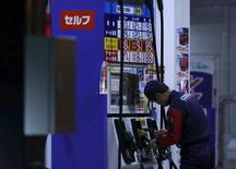 An employee of Cosmo Energy Holdings' Cosmo Oil service station checks its nozzles at a branch in Tokyo, Japan, December 16, 2015. REUTERS/Yuya Shino