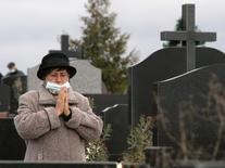 Женщина в медицинской маске молится на кладбище в украинском Тернополе 1 ноября 2009 года. Десять человек погибли от свиного гриппа (H1N1) в последние два месяца в Армении, сообщила представитель Минздрава, добавив, что не рассматривает случившееся как эпидемию. REUTERS/Viktor Gurniak