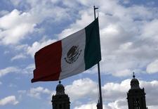 La bandera de México ondea cerca de la Catedral Metropolitana en la Plaza del Zócalo en Ciudad de México. 26 de agosto de 2015. El Gobierno de México anunció el miércoles la colocación de un bono a 10 años por 2,250 millones de dólares, en una operación que tuvo un fuerte interés de inversionistas internacionales pese al entorno de incertidumbre y volatilidad global. REUTERS/Henry Romero