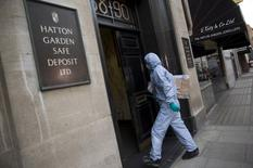 A police forensic officer enters a safe deposit building on Hatton Garden in central London April 7, 2015. REUTERS/Neil Hall