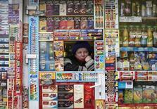 Продавец в ларьке в центре Киева 21 января 2015 года. Руководители украинских предприятий не разделяют оптимизма денежных властей Украины и ожидают более высокую инфляцию и большее снижение курса гривны в 2016 году, свидетельствуют данные ежеквартального опроса, проведенного Национальным банком. REUTERS/Gleb Garanich