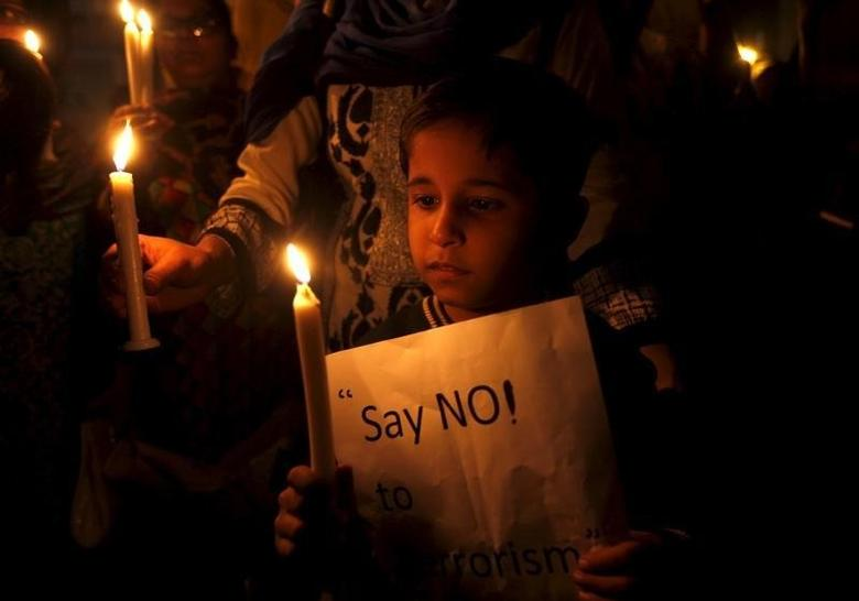 A child holds a candle and sign against terrorism at a vigil in Karachi, Pakistan, December 16, 2015 in commemoration of the anniversary of the Taliban attack on the Army Public School in Peshawar. REUTERS/Akhtar Soomro