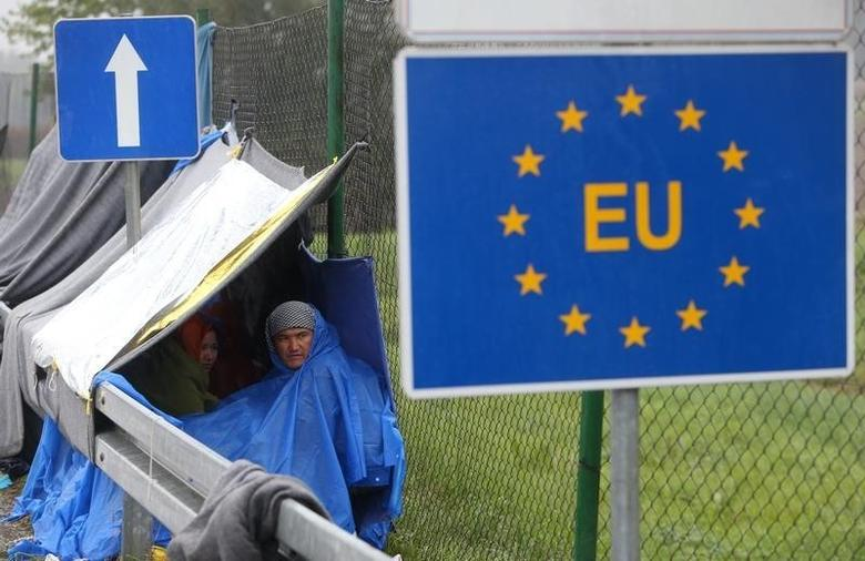 An EU sign is seen as migrants wait in the no man's land to cross the border to Slovenia from Trnovec, Croatia, October 19, 2015. REUTERS/Srdjan Zivulovic