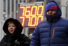 Люди идут на фоне таблички с курсами обмена рублей к доллару в Москве 12 января 2016 года. Рубль подешевел в среду до отметки 80,93 за доллар впервые в новейшей истории с учетом деноминации 1998 года, отражая снижение нефтяных цен на многолетние минимумы на фоне переизбытка предложения на нефтяном рынке. REUTERS/Sergei Karpukhin