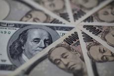 Un billete de 100 dólares estadounidenses junto a billetes de 10,000 yenes japoneses, en Tokio. 28 de febrero de 2013. El dólar tocó mínimos de más de un año contra el yen el miércoles, debido a la caída de los precios del petróleo a su nivel más bajo en casi 13 años y ante un retroceso del apetito por el riesgo. REUTERS/Shohei Miyano
