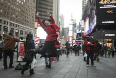 A tourist jumps in the air as she poses for a photo in Times Square during unseasonably warm weather on Christmas eve in New York, in this file photo taken December 24, 2015.    REUTERS/Carlo Allegri/Files